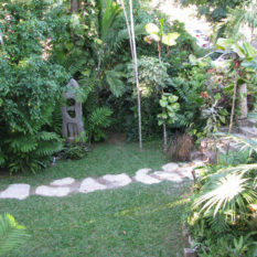 View of music man in the gardens of Villa Ronai from patio of the suites